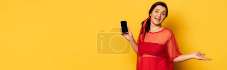 pregnant woman in red outfit holding smartphone with blank screen on yellow, website header
