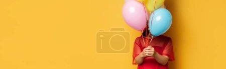 Foto de Imagen horizontal de la mujer embarazada en la túnica roja que oscurece la cara con globos festivos multicolores en amarillo - Imagen libre de derechos