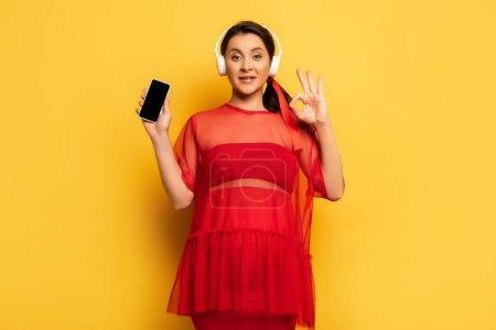 Photo pour Femme enceinte dans des écouteurs sans fil montrant smartphone et geste correct sur jaune - image libre de droit