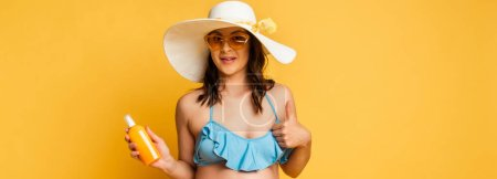 Photo for Young woman in sunglasses and straw hat holding sunscreen and showing thumb up on yellow, horizontal image - Royalty Free Image