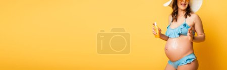 Photo for Cropped view of pregnant woman applying sunscreen on belly while posing on yellow, panoramic shot - Royalty Free Image