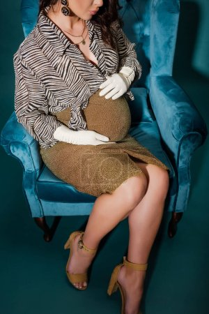 Photo pour Vue partielle de la femme enceinte dans des vêtements à la mode touchant le ventre tout en étant assis dans un fauteuil en velours sur bleu foncé - image libre de droit