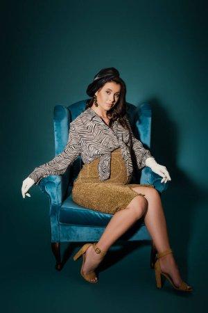 Photo pour Femme enceinte à la mode assise dans un fauteuil en velours et regardant la caméra sur bleu foncé - image libre de droit