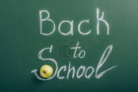 Photo pour Vue du dessus de la pomme mûre près du lettrage de retour à l'école sur un tableau vert - image libre de droit