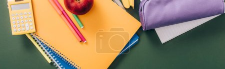 Photo for Top view of multicolored notebooks and school supplies on green chalkboard, horizontal image - Royalty Free Image