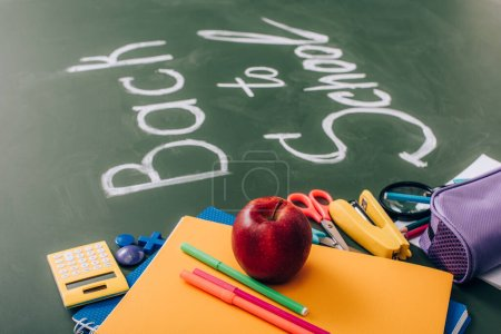 selective focus of school stationery and fresh apple near back to school inscription on green chalkboard