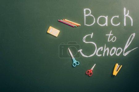 Photo pour Vue du haut de l'inscription de retour à l'école près de la papeterie scolaire sur un tableau vert avec espace de copie - image libre de droit