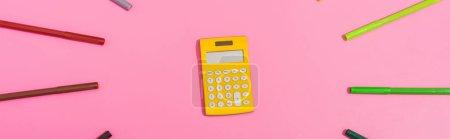 Photo pour Vue du haut de la calculatrice dans le cadre de stylos couleur feutre sur rose, image horizontale - image libre de droit