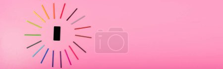 Photo for Top view of smartphone with blank screen in frame of color felt-tip pens on pink, panoramic concept - Royalty Free Image