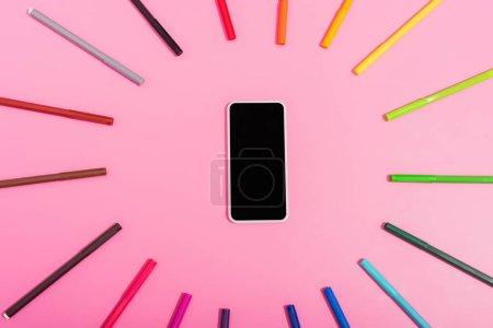 Photo pour Vue du haut du smartphone avec écran vierge encadré par des stylos couleur feutre pointe sur rose - image libre de droit