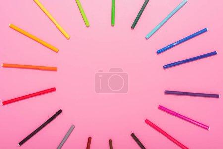 Photo pour Vue du dessus du cadre circulaire de stylos feutre multicolores sur rose avec espace de copie - image libre de droit