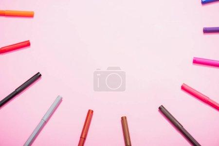 Photo pour Cadre de stylos feutre couleur sur fond rose avec espace de copie, vue du dessus - image libre de droit