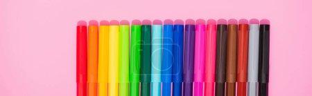 Photo pour Plan panoramique de crayons feutre couleur rangée sur fond rose, vue de dessus - image libre de droit