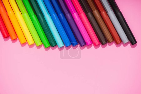 Photo for Top view of color felt-tip pens set on pink background with copy space - Royalty Free Image