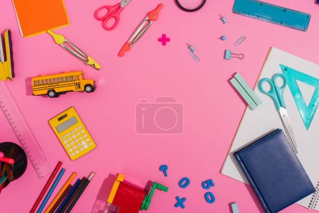 Photo for Top view of school supplies and school bus model on pink with copy space - Royalty Free Image