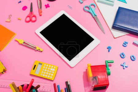 Photo for High angle view of digital tablet near notebooks and school supplies on pink - Royalty Free Image