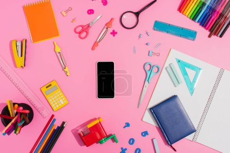 Photo for Top view of smartphone with blank screen surrounded by school supplies on pink - Royalty Free Image