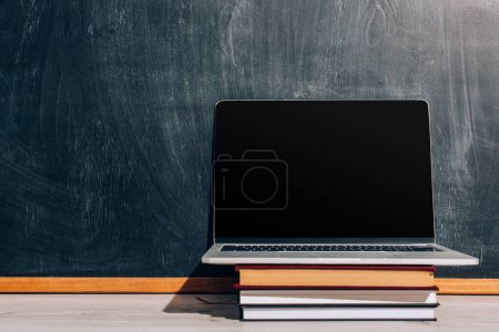 laptop with with blank screen on stack of textbooks near black chalkboard