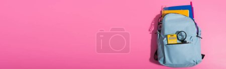 Photo for Top view of blue backpack full of school supplies on pink with copy space, horizontal image - Royalty Free Image