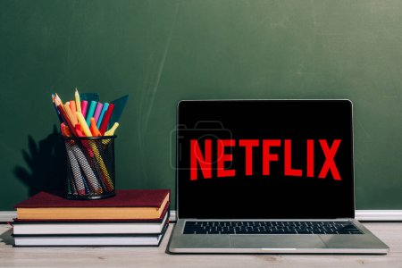 Photo for KYIV, UKRAINE - JULY 7, 2020: Laptop with Netflix website near pen holder with stationery on stack of books near green chalkboard - Royalty Free Image