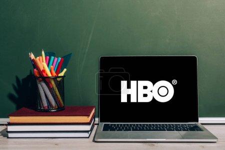 Foto de KYIV, UCRANIA - 7 de julio de 2020: Portátil con sitio web de HBO cerca del portalápices con artículos de papelería en la pila de libros de texto cerca de pizarra verde - Imagen libre de derechos