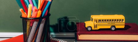 Photo for Horizontal image of school bus model on books near pen holder with stationery on notebook near green chalkboard - Royalty Free Image
