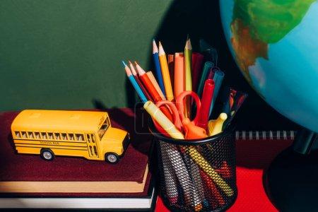 Photo pour Modèle d'autobus scolaire sur les livres, porte-stylo avec papeterie et globe près de tableau vert - image libre de droit