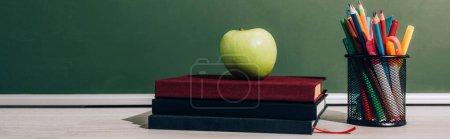 Photo pour Image horizontale de pomme mûre sur des livres près du porte-stylo avec des crayons de couleur près du tableau vert - image libre de droit