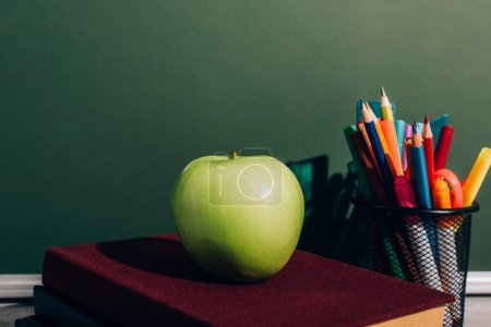 Photo for Whole apple on books near pen holder with color pencils and felt pens on desk near green chalkboard - Royalty Free Image