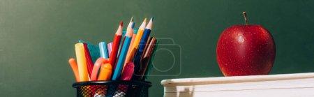 Photo pour En-tête de site Web du porte-stylo avec crayons de couleur et stylos, et pomme mûre sur les livres près du tableau vert - image libre de droit