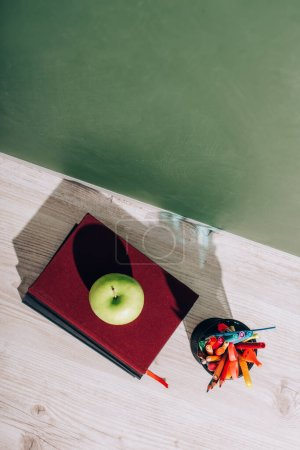 Photo pour Vue grand angle de la pomme entière sur les livres près du porte-stylo avec papeterie sur le bureau près du tableau vert - image libre de droit