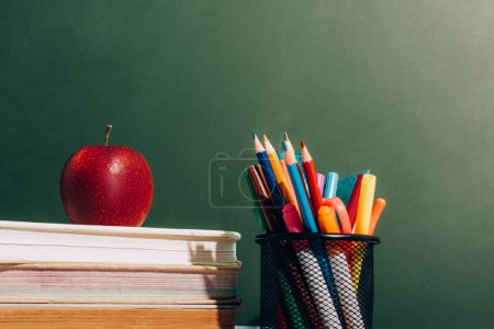 Photo for Pen holder with color pencils and felt pens and ripe apple on books near green chalkboard - Royalty Free Image