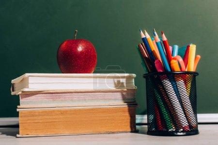 Photo pour Pomme mûre sur les livres et porte-stylo avec crayons de couleur et stylos en feutre sur le bureau près du tableau vert - image libre de droit
