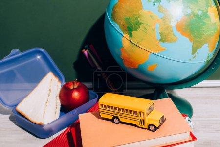 Photo pour Globe près de la boîte à lunch et le modèle d'autobus scolaire sur les livres près de tableau vert - image libre de droit