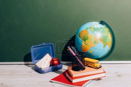 Photo pour Globe près de la boîte à lunch, livres, porte-stylo et bus scolaire modèle un bureau près de tableau vert - image libre de droit