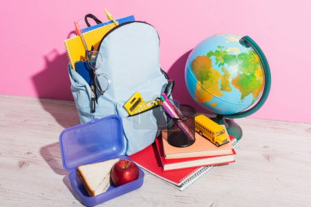 Photo for Blue backpack with school supplies near globe, lunch box, books, pen holder and school bus model on pink - Royalty Free Image