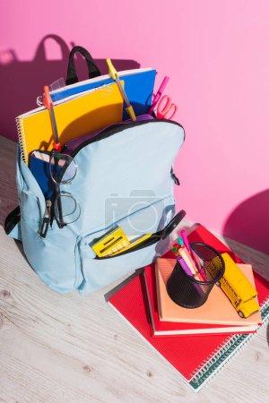Photo pour Vue grand angle du sac à dos plein de fournitures scolaires près des livres, porte-stylo et modèle d'autobus scolaire sur rose - image libre de droit