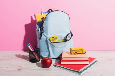 Photo for Full backpack with school stationery near toy school bus on books, ripe apple and pen holder on pink - Royalty Free Image