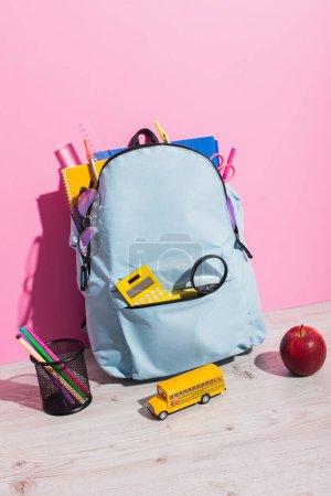 Photo pour Sac à dos scolaire rempli de papeterie près du modèle d'autobus scolaire, pomme entière et porte-stylos en feutre rose - image libre de droit