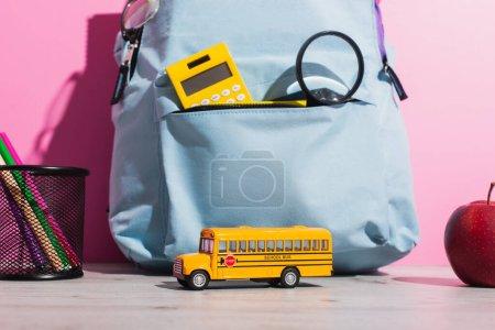Photo pour Sac à dos bleu avec fournitures scolaires près du modèle d'autobus scolaire, pomme mûre et porte-stylo avec stylos en feutre rose - image libre de droit