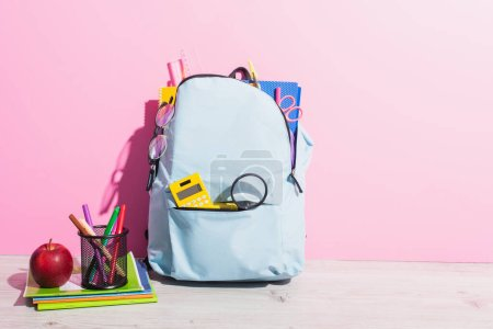 Photo pour Sac à dos scolaire plein de papeterie près de livres de copie, pomme et porte-stylo avec stylos en feutre sur rose - image libre de droit