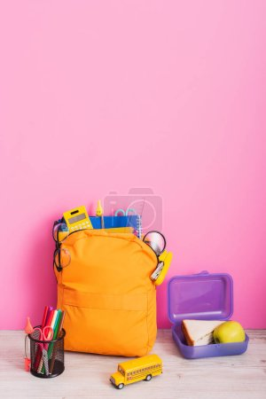 yellow backpack with school supplies near lunch box, school bus model and pen holder with felt pens on pink