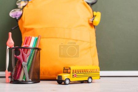 yellow backpack near school bus model, pen holder with felt pens, scissors and compass divider on desk near green chalkboard