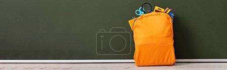 Photo pour Image horizontale du sac à dos jaune plein de papeterie scolaire sur le bureau près du tableau vert - image libre de droit