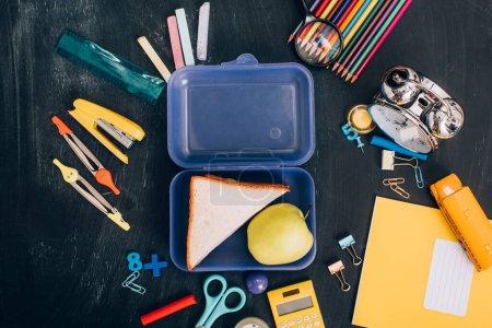 Photo pour Vue du dessus de la boîte à lunch avec pomme et sandwichs près du réveil rétro et fournitures scolaires sur tableau noir - image libre de droit