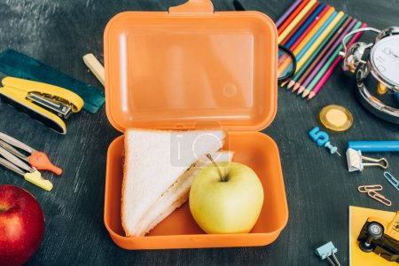 top view of lunch box with sandwiches and ripe apple near school stationery on black chalkboard