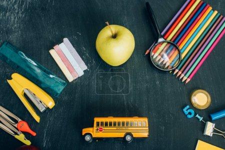 Photo pour Vue du dessus du modèle d'autobus scolaire, de toute la papeterie de pomme et d'école sur le tableau noir - image libre de droit