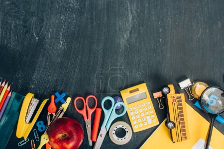 top view of school bus model, ripe apple and school supplies on black chalkboard with copy space
