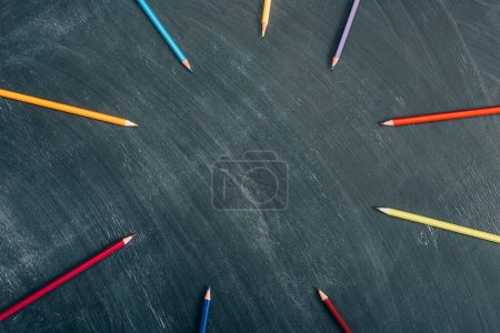 Photo for Top view of circle frame of color pencils on green chalkboard - Royalty Free Image