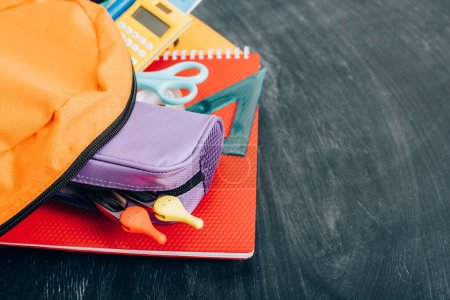 Photo pour Sac à dos jaune avec papeterie scolaire multicolore sur tableau noir - image libre de droit